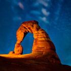 Dramatic side lighting after sunset accentuates the well known and well worn Delicate Arch in Arches National Park, Utah.