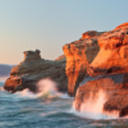 Late sun shines on the cliffs of Cape Kiwanda and illuminates crashing waves as fog rolls in over the distant hills.