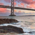 While millions of people each year come to visit the world famous Golden Gate Bridge in San Francisco, across the Bay, another beautiful Bridge begs to be photographed as well.  Here, the Bay Bridge stands stoic between receeding waves and glowing clouds.