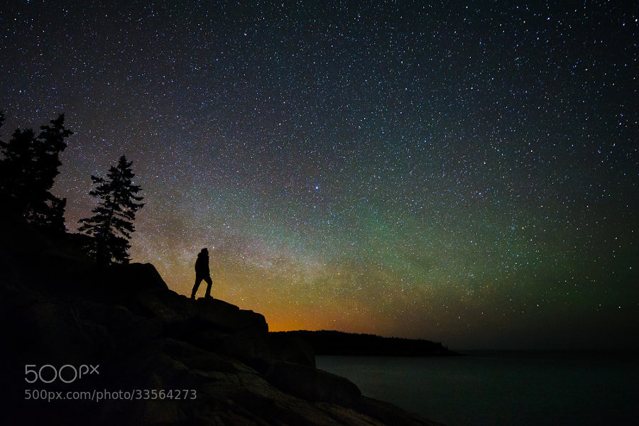 The rising Milky way and some green airglow provide a nice backdrop for a stargazer's silhouette at Acadia National Park, Maine.