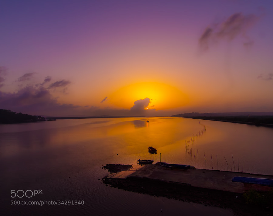 The sun was just up and covered by clouds. The golden rays could be traced along the Mandovi River,Goa.