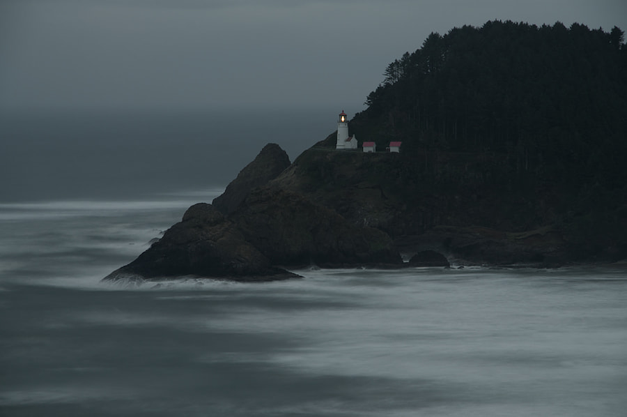 Heceta Head Lighthouse just before dawn on a cloudy morning.