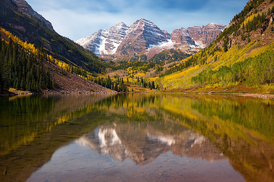 """Nestled into the magnificent Snowmass Wilderness in Colorado, Maroon Lake gracefully reflects what are widely considered the most photographed peaks in North America...the """"Fourteeners"""" known as the Maroon Bells.  The Maroon Bells are actually one mountain with two peaks. The South Maroon Peak is the 27th highest peak in Colorado, and North Maroon Peak is the 50th highest. The stunning Bells achieve their amazing color from their composition of ancient mudstone.  Even such a popularly photographed location can result in a fresh impression. This view was captured immediately after the skies released a dusting of snow on the Snowmass peaks, as if to warn of winter's coming. Maroon Lake serenely reflects back the richly detailed, pristine panorama, causing the scene to glow with a remarkable light fueled by the amazing autumn color of Colorado's Aspen groves and evergreen forests."""