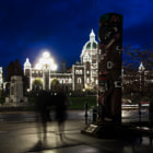 Two people walk past a totem pole in the blue hour. Inner harbour, Victoria, BC, Canada, a war memorial and the provincial legislature buildings in the background.