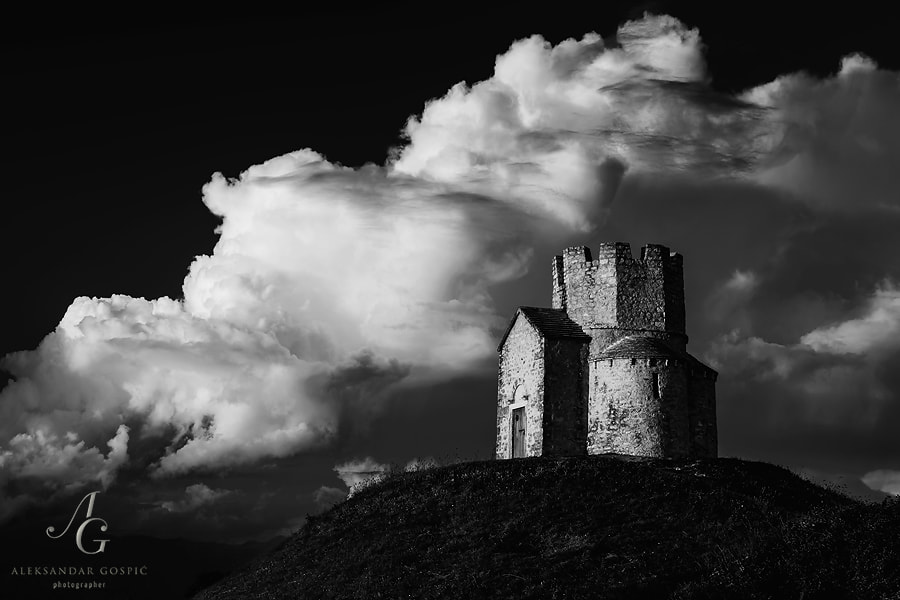 Sveti Nikola u Prahuljama church from 11th century, near Nin town, poses against the cumulonimbus cloud on the Velebit mountain