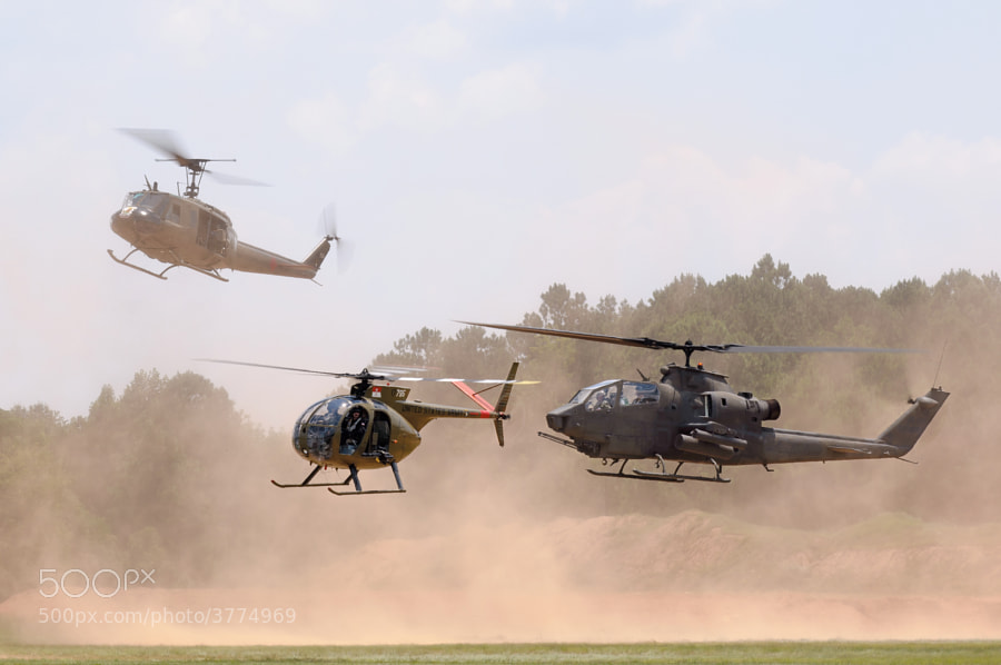 The Sky Soldiers demonstration team - A Huey, Cobra and Loach kick up massive amounts of dust as they hover above the LZ