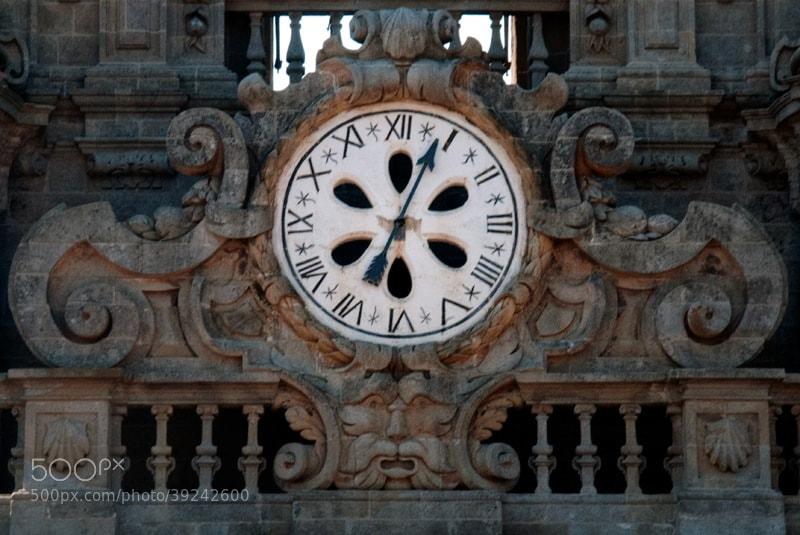 """Camino de Santiago 2012  Monte del Gozo - Santiago V _______________________________  El reloj de una sola aguja, en los tejados de la Catedral. _______________  The clock of a single hand, on the roof of the Cathedral. __________  La Torre del Reloj  de la Catedral de Santiago de Compostela, se llama Torre de La Trinidad  Su construccion fue como Torre defensiva.   El Obispo Diego de Padrón fue quien ordenó su construcción allá por el Siglo XIV.   El nombre de Torre de la Berenguela, o el de la Campana Berenguela (la campana mayor de la Torre)   tiene su origen en Berenguer Landoira (quien terminó la construccion) .   Mucho más tarde, ya en el S. XVII, el maestro Domingo de Andrade diseñó los dos cuerpos superiores que a día de hoy adornan la Torre. Esta decoración esta basada en motivos vegetales, y como no , motivos relacionados con la ruta Jacobea  .   El reloj fue construido en 1831 por encargo del Arzobispo Rafael Vélez.  Consta de  cuatro esferas, que van respectivamente orientadas en cada cara de la Torre .  Una de las mayores peculiaridades del reloj, es que cuenta con sólo una aguja, ya que las horas las marca la famosa Berenguela , y los cuartos su compañera.  Desgraciadamente , las que se usan hoy en día son réplicas de las originales, pues con el paso del tiempo, tanto la Berenguela como la campana de los cuartos , sufrieron diversas grietas que afectaron al sonido, y fueron  sustituidas  definitivamente en el año 1990  Todo aquel que quiera ver las originales , tendrá que acceder a los museos de la Catedral , ya que se exponen en el Claustro.  La """"Berenguela"""" original fue fundida en 1729 por Güemes Sampedro, un famoso fundidor de la época .  Pesa la nada despreciable cifra de casi 10 Toneladas (unos  9600 kilos aproximadamente) Su diámetro es de  256 cm. y una altura de 216 cm. Su afinación es en """" Do """" Algunos detalles  sobre su decoración son  una cruz patriarcal con el calvario de Jesucristo ,  un cuadro sobre la batalla de Clavijo (la famosa en la """