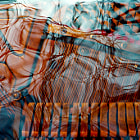 One of a number of experimental images created on film, over 20 years ago.   It is meant to evoke a piano under water, this is an in-camera double-exposure on film. It shows piano hammers, strings, and tuning pins, combined with tree branches reflected on the surface of a pond.  Two exposures on the same frame of film.  Scanned from a 35mm negative.