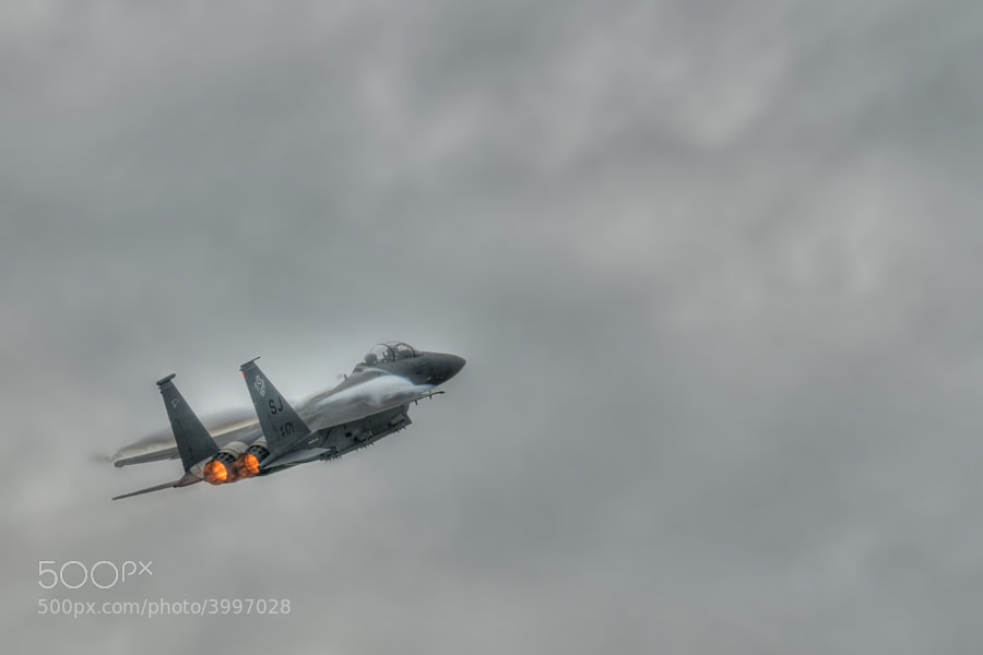 An F-15E Strike Eagle climbs rapidly into stormy skies.