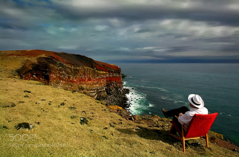 """The name of this beautiful and colorful cliffs is Krýsuvíkurbjarg, and it is about 70 m high. The """"handsome"""" model who is sitting there on the edge of the cliff is me."""