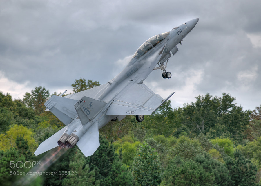 An F/A-18 Super Hornet blasts off the runway under a low cloud deck to begin its flight demonstration