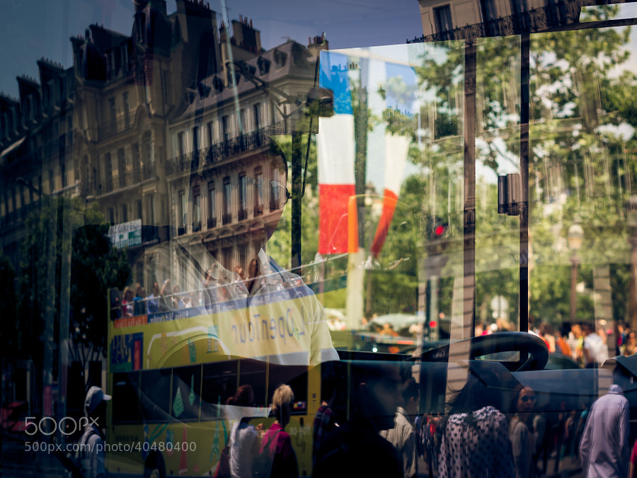 I took this picture at the Champs-Elysees while crossing the street. It is through the front window of a bus with refelctions of another tourist bus as well as one of the flags that are placed at the side of the Avenue