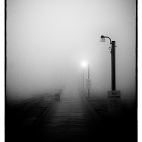 One of the jetties in Galveston Texas on a very foggy morning just before Sunrise. This particular jetty leads out to a fishing pier. I think the fog makes for a somewhat haunting image.