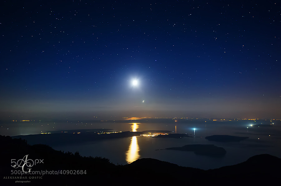 Moon, which is nearing the end of its journey across the sky, shines above the islands of North Adriatic and Istria peninsula, viewed from the altitude of 1600m on Velebit mountain.