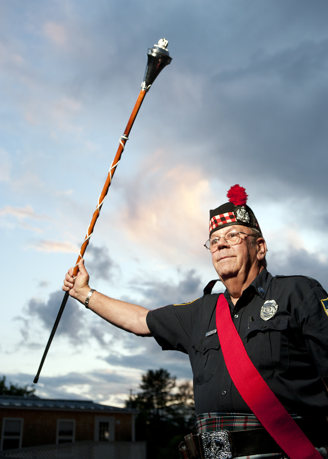 Drum Major Vaughn Dyer of the Maine Public Safety Pipe & Drum Corp raises his mace to signify the end of a song.