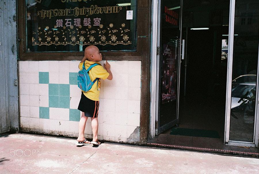 A kid peeping outside a barber shop.