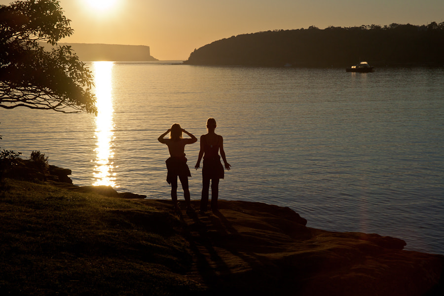 Two women watch the sun rise over Hunter's Bay and Balmoral Beach near Sydney.