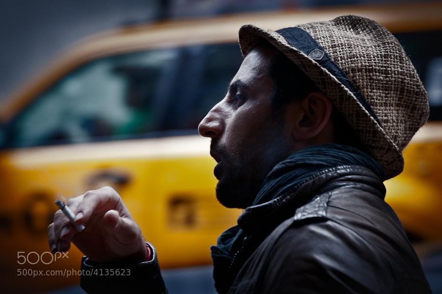 A man standing on the side of a street in SoHo having a smoke as a yellow taxi passes by.