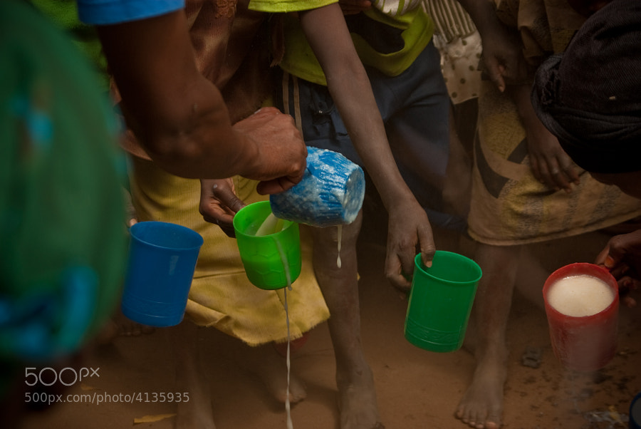 """One of the very favorite images I have captured. This is a feeding station near the border town of Garissa, Kenya. Looking at this picture instantly brings back the press of the crowd, the grit of the earth, the smell of the porridge, the heat of the hair, and the sounds of the children wanting it to be their turn. The organization """"Feed my Babies"""" uses this image in their promotional material."""