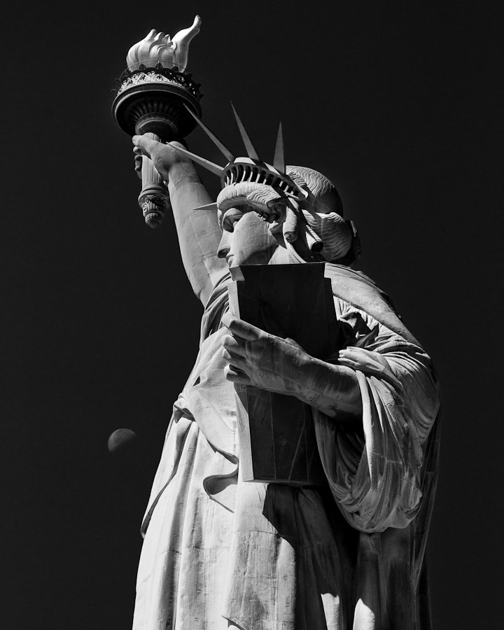 The setting moon is seen next to the Statue of Liberty