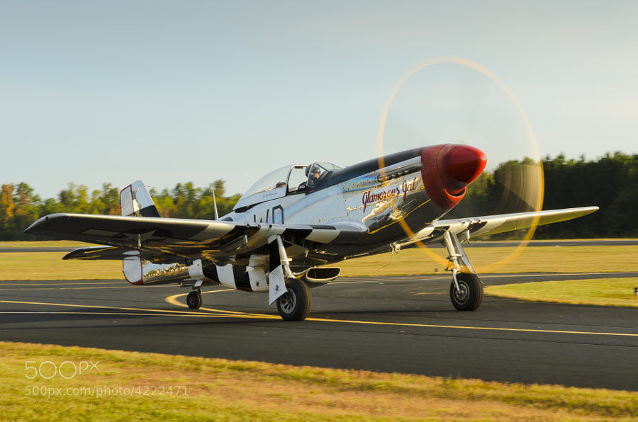 "The setting sun gleams off of the propeller of the P-51D Mustang ""Glamorous Gal"" as it taxis for takeoff at the end of the ""Great Georgia Airshow"""