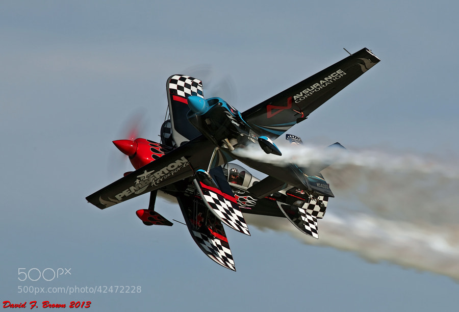 Two of the world's best aerobatic performers, Skip Stewart and Melissa Pemberton, perform at Air Venture (Oshkosh) 2013.  Although it appears Skip is being photo bombed by Melissa, this is actually a well choreographed part of their joint routine.