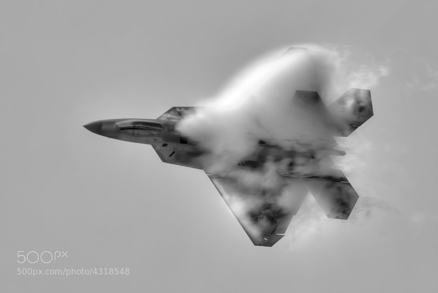 "Vapor surrounds Maj. Paul ""Max"" Moga as he makes a high speed pass in the F-22A Raptor."