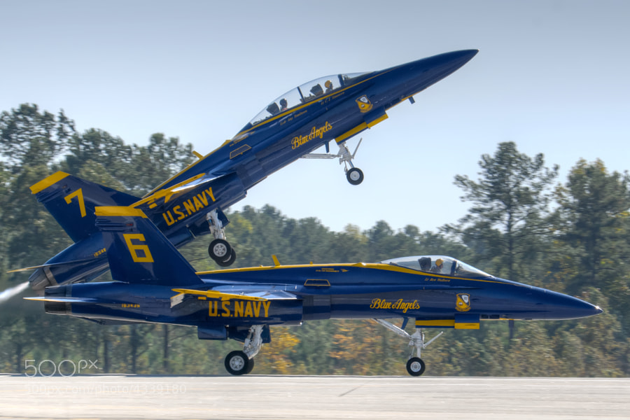 The Blue Angels #7 solo aircraft pulls up sharply to begin a practice session at Dobbins ARB. One of the CAF Snowbirds pilots is getting a ride in the backseat.