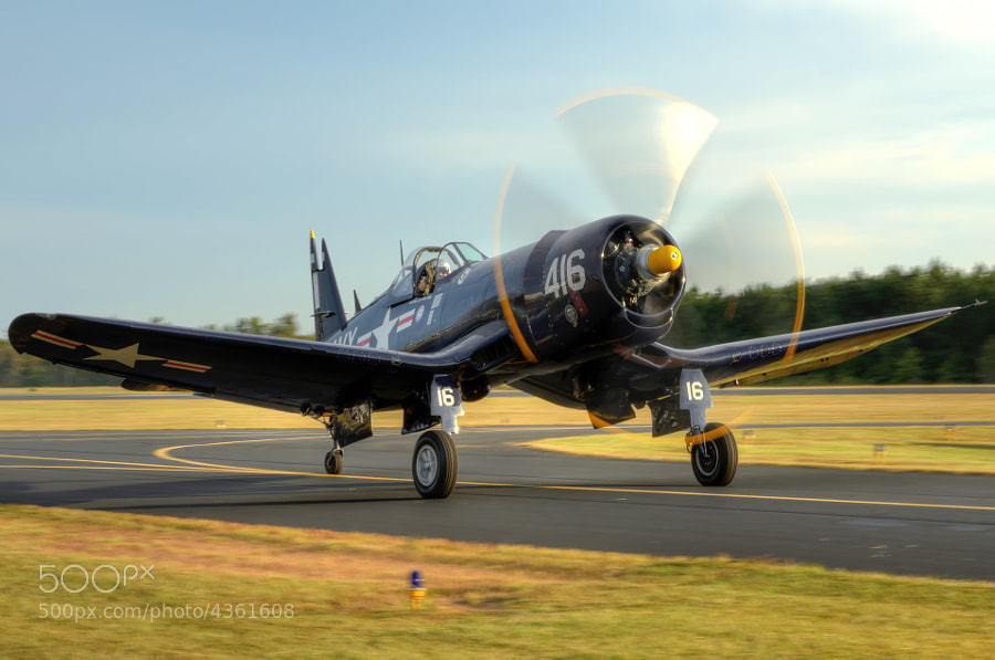 The setting sun shines off a pristine WWII era F4U Corsair as it taxis for takeoff at The Great Georgia Airshow