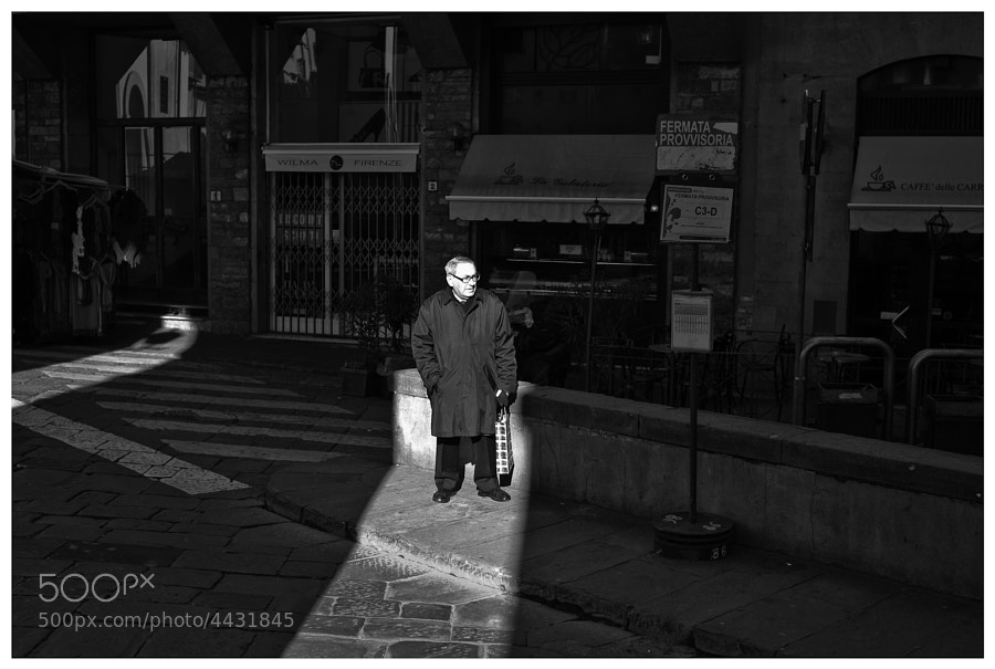 Man waiting at a bus stop is illuminated by a shaft of sunlight