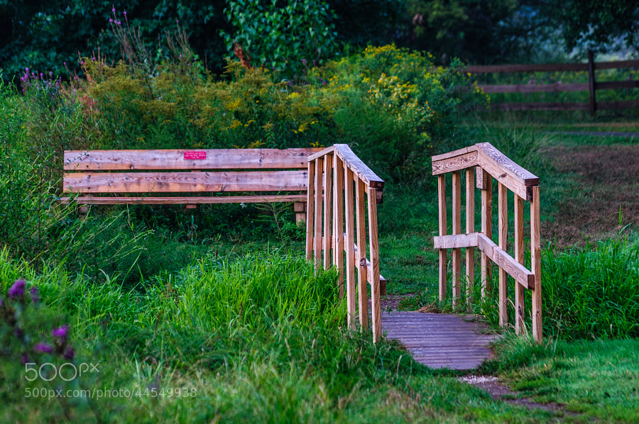 Over the small man made Bridge, the seat to gaze upon the Pond.