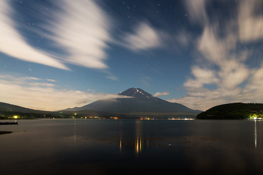 This is Mt.Fuji in summer night. I took this photo at lakeside of Yamanakako in Yamanashi pref. Japan. (taken at 3:22 AM)  Bright lines on Mt.Fuji are light of climbers.