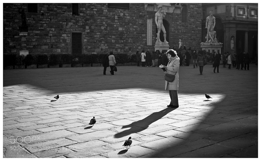 A woman tourist checks out her guide book in the Piazza della Signoria, Florence
