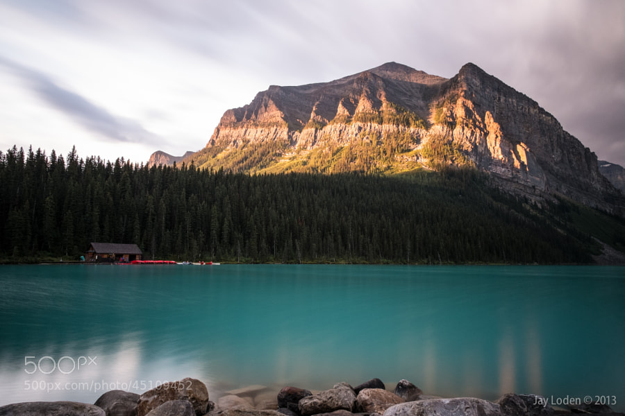 Sunrise at Lake Louise - the sun rises over a forest and other mountain ranges to dramatically light part of the scene.  Lake Louise, Banff National Park, Alberta Canada