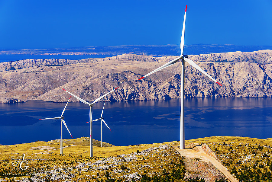80m high wind turbines on the plateau Vrataruša, 700m above the Adriatic Sea, pose in front of the 400m high wall of the Krk island. For a sense of space there are cyclists under the right windmill