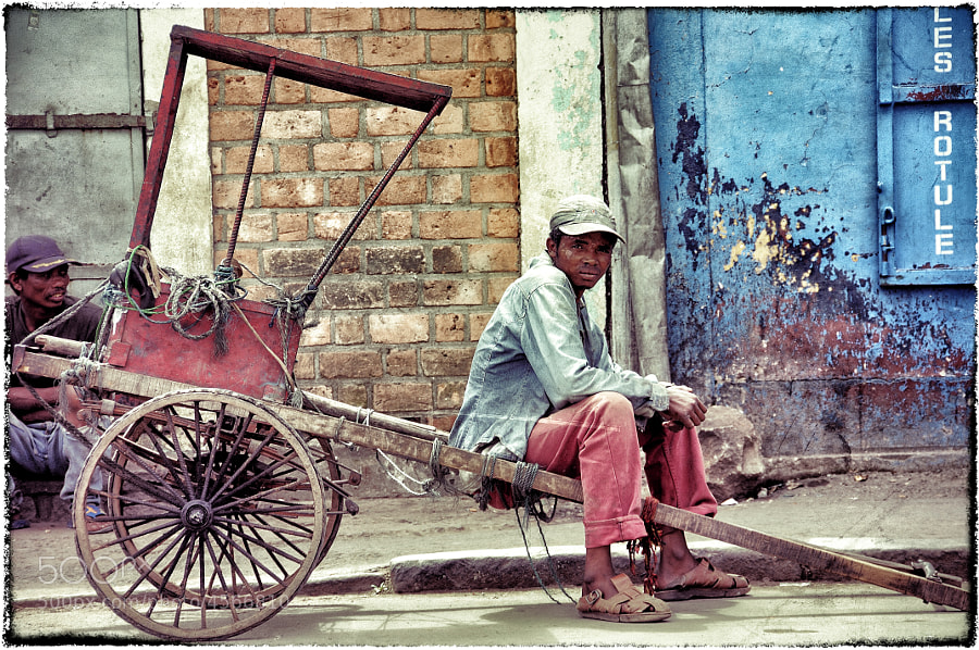 A young man waiting for a fare on a street in Antananarivo, Madagascar