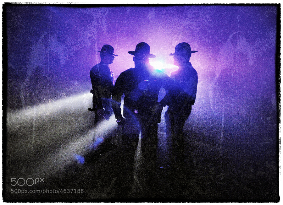 Oklahoma Highway Patrol Officers discuss evidence at a one vehicle roll-over accident on a very foggy evening.