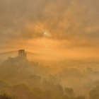Corfe Castle in the early morning mist.