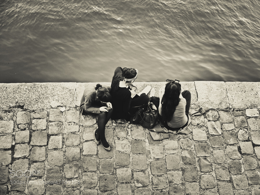 Parisian girls having a break on the bank in front of the Seine.