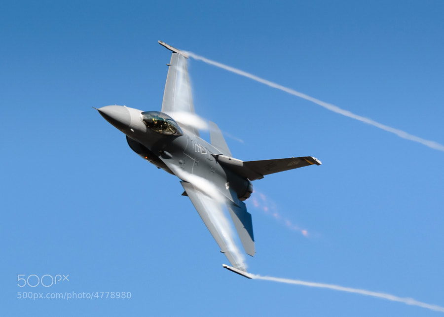 "Vapor flows off the wings of this F-16 Fighting Falcon or ""Viper""   during the dedication pass at NAS Pensacola"