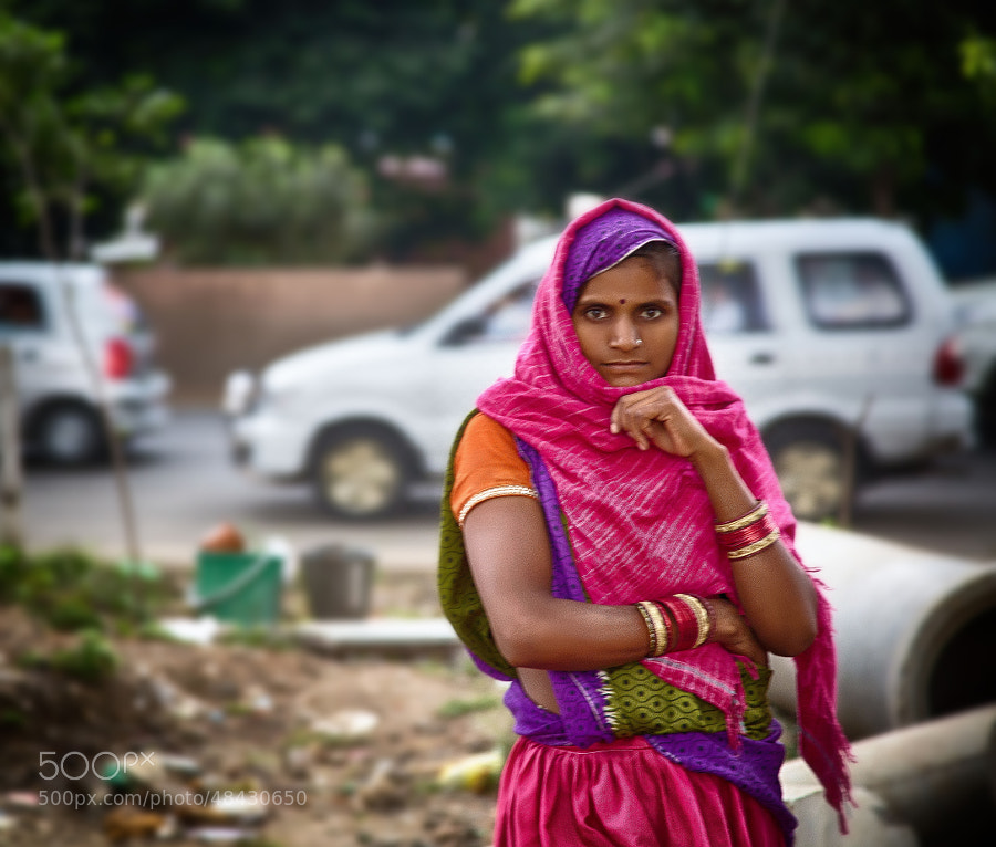 Digital color image of woman on a street corner wearing pink sari in Indore, India