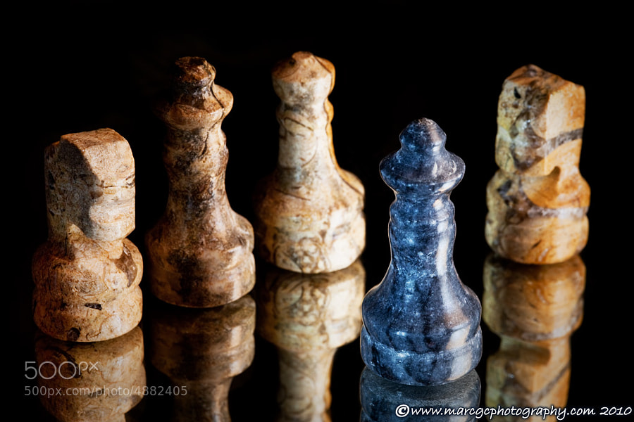 A macro shoot of a tiny marble chess pieces reflected on a mirror. The black king has been surrounded and defeated. As always the black sheep get the worst part.
