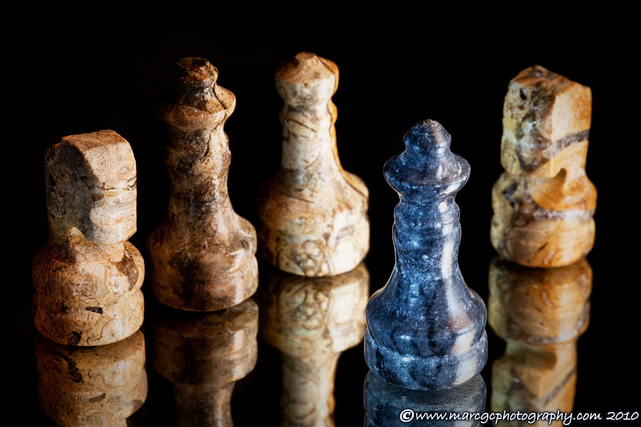 "Join me on my <a href=""https://www.facebook.com/marcgcphotography"" rel=""nofollow"">Facebook Page</a>.  A macro shoot of a tiny marble chess pieces reflected on a mirror. The black king has been surrounded and defeated. As always the black sheep get the worst part."