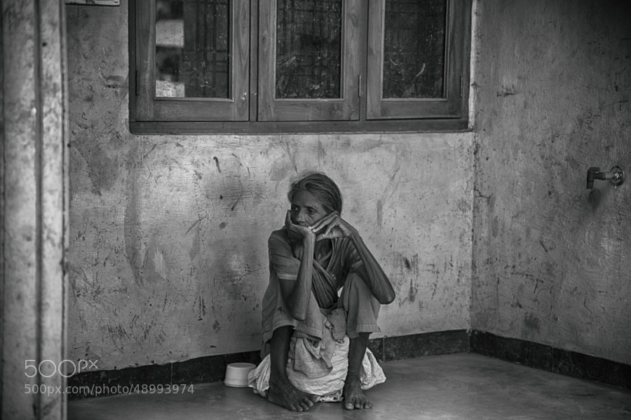 Digital black & white image of an elderly woman sitting on her belongings in small alcove on a corner (Indore, India)