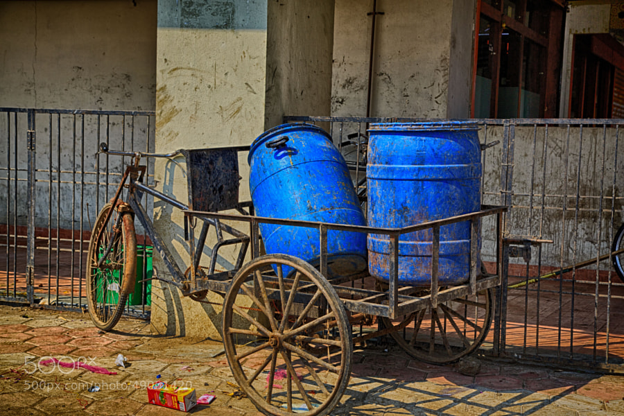Digital color image of blue drums on a three-wheeled cart o na street corner in India (Indore, India)