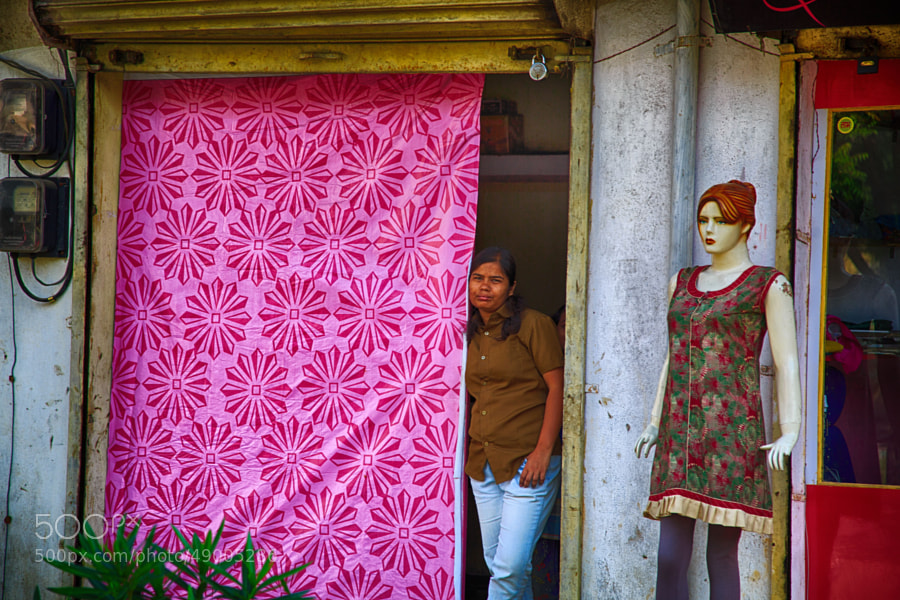 Digital color image of a woman on a side street in India staring from her doorway, with a mannequin standing nearby (Indore, India)
