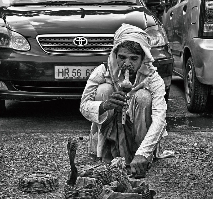 Digital b&w image of a snake charmer on a street corner in  Delhi, India