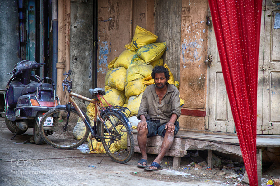 Digital color image of a seemingly tired man on a wooden porch in an alleyway (Indore, India).