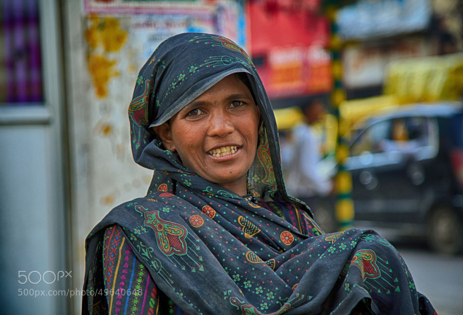 Digital color image of a woman with a piercing smile, with a small child tucked beneath her traditional outfit, on a street corner in Indore, India