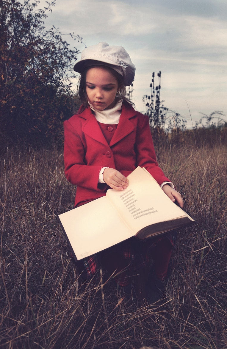 Photograph Kid with red coat  and a book by Kiril Stanoev on 500px